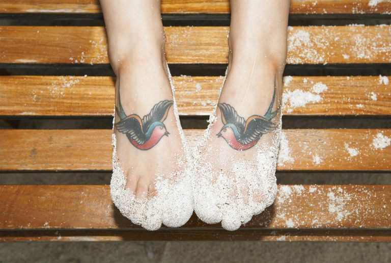 Sand and two tattooed swallows on woman's feet