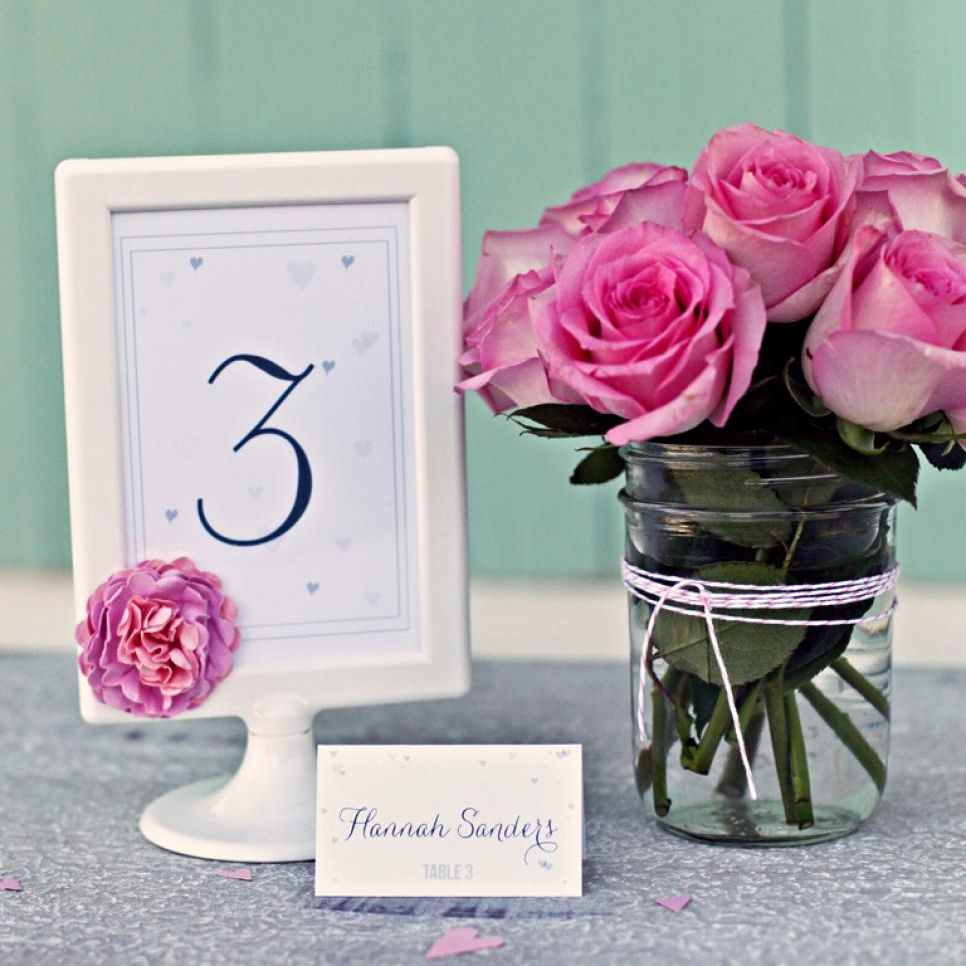 A wedding place card in a frame next to a vase of roses.