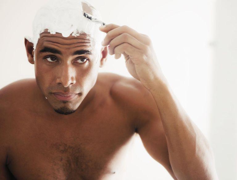 A black man shaving his head