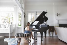 Girl (10-11) playing piano in living room