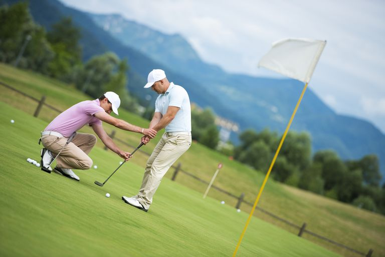 Golf teaching professional giving putting tips to a student golfer