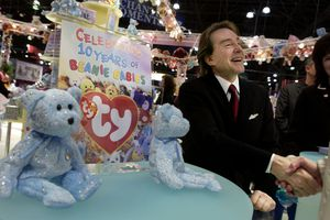 Ty Warner seated at a table with Beanie Babies and celebratory sign