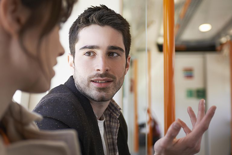 Man talking to woman in train