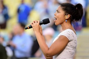 Karla Mosley in profile holding a microphone.