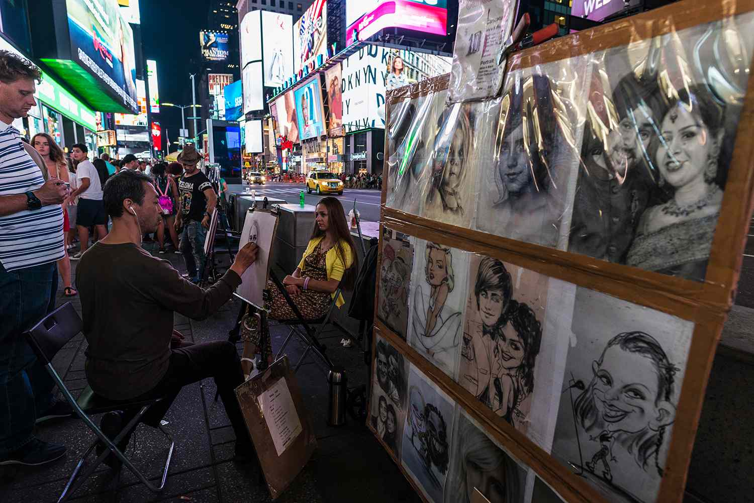 Cartoonist doing a portrait in pencil to a girl on Times Square