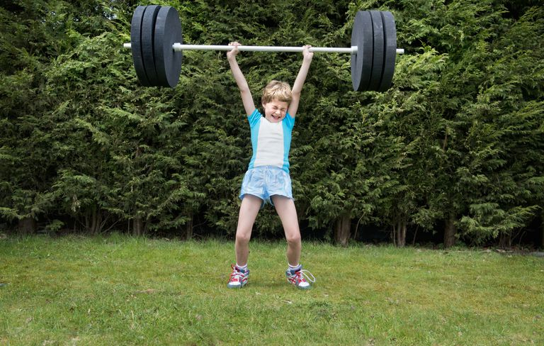 Strong boy lifting heavy weights