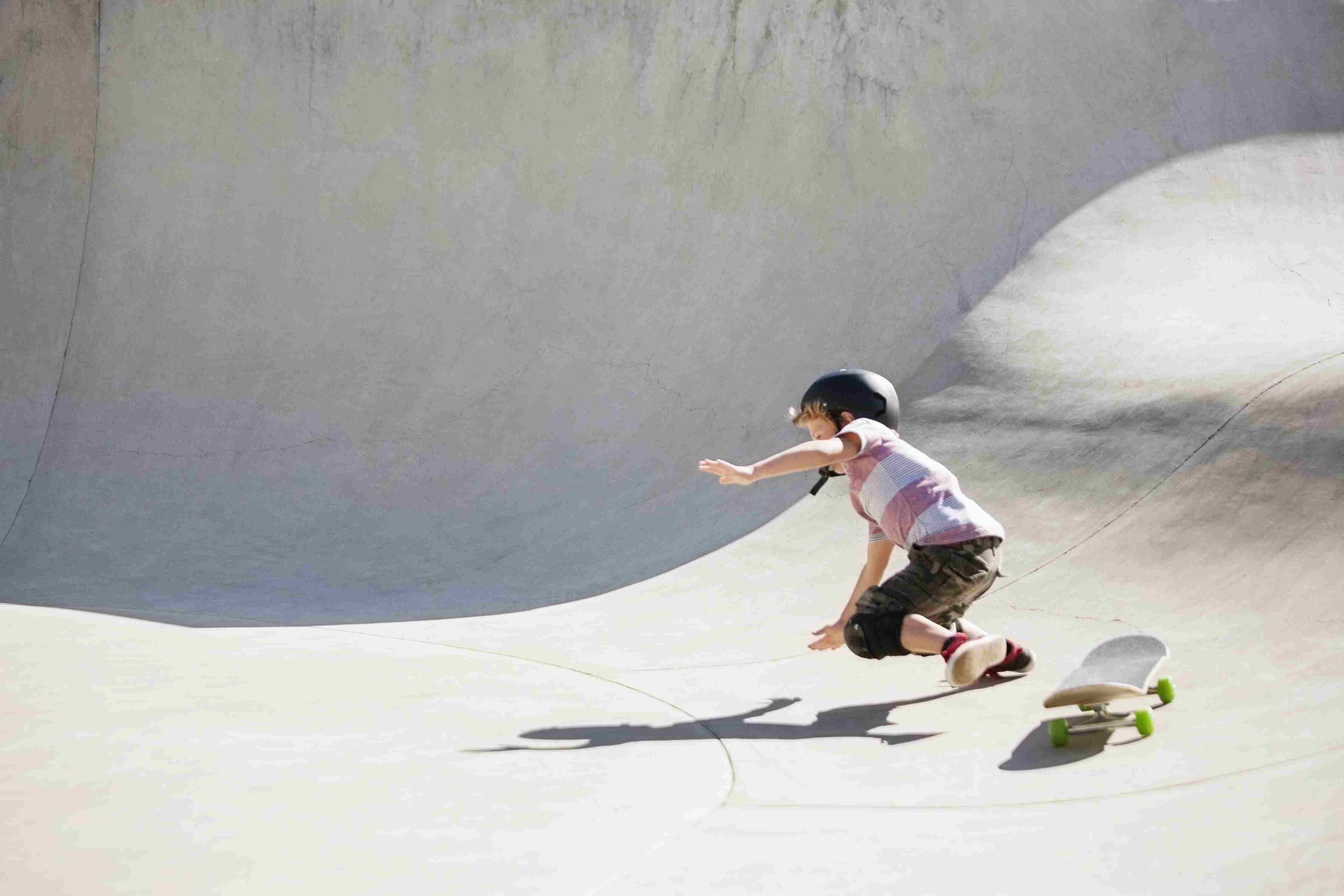 Boy falling on skateboard ramp