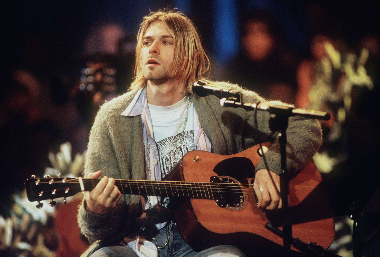 Kurt Cobain singing and playing guitar on stage.