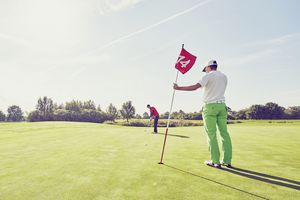 Two golfers on a green, one holding the flagstick while the other putts