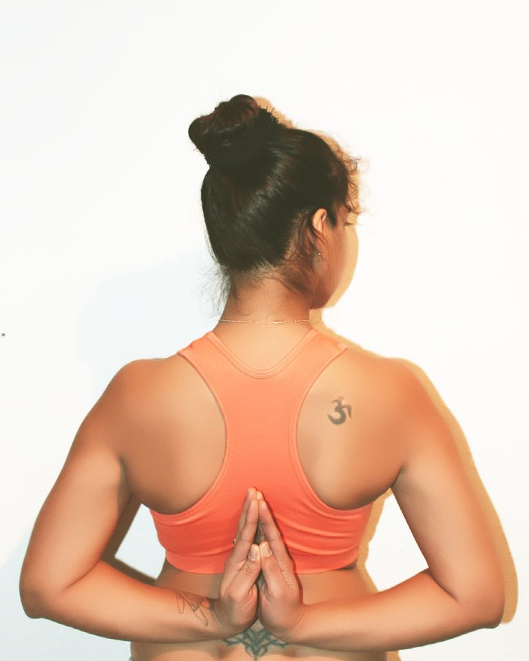 Young brown woman holding her hands behind her back with an om tattoo on her shoulder