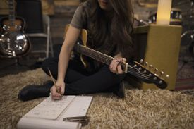 Young woman with guitar writing music.