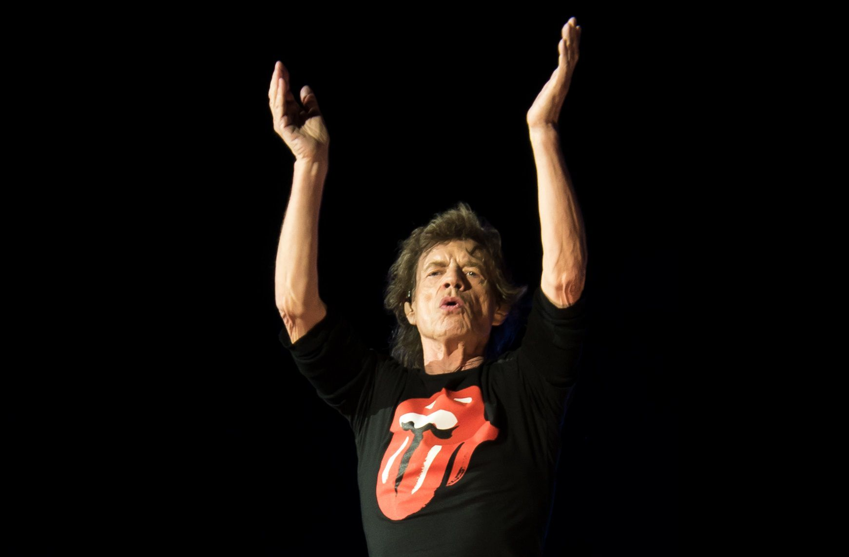 Mick Jagger performing on a darkened stage.