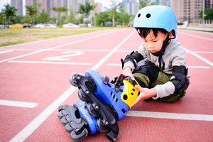 Little boy wearing roller-blades.