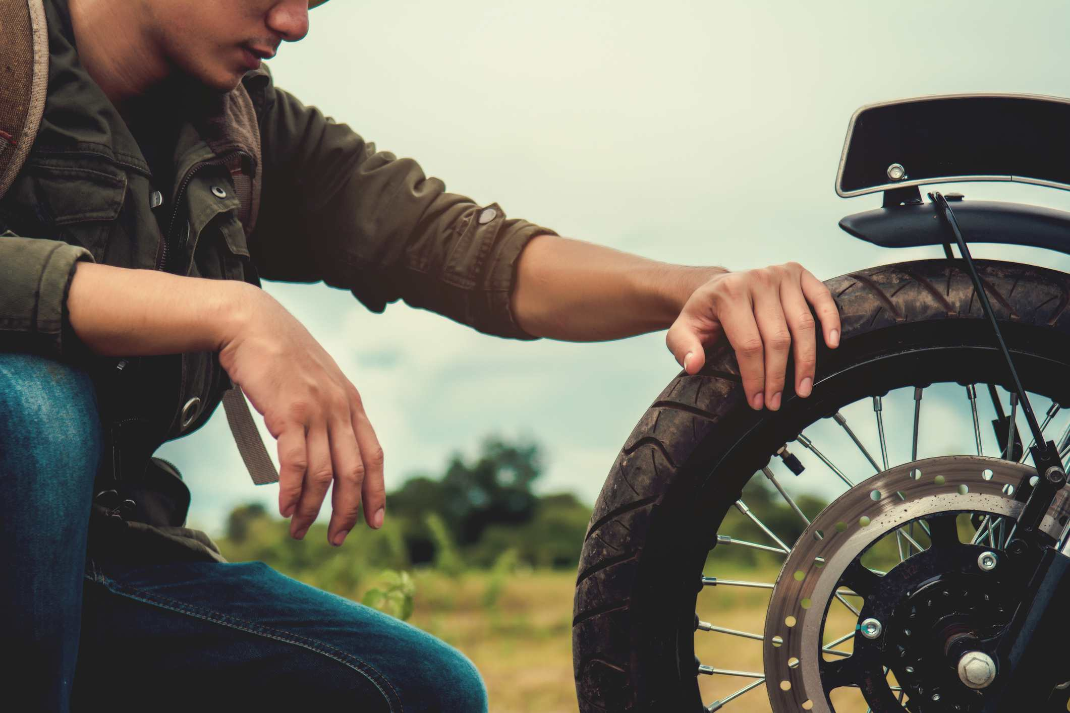 Side View Of Young Man Looking At Tire Of Motorcycle
