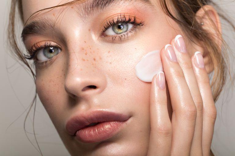 model massaging cold cream onto her skin