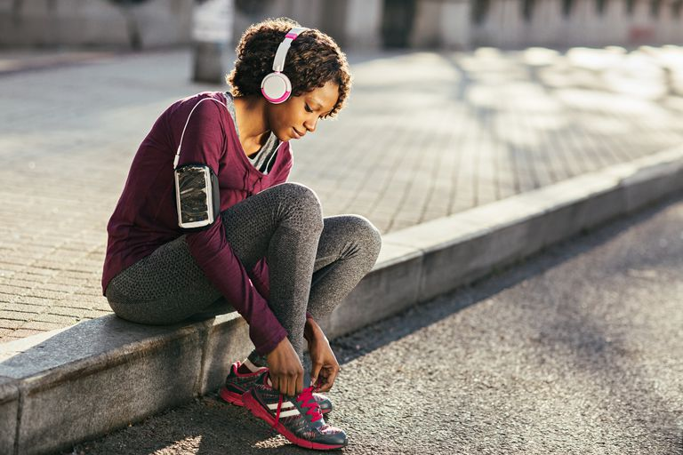 Photo of a young exercising woman tying her shoelace