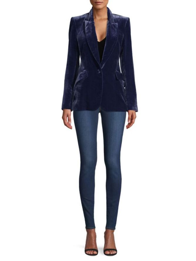 cf8a9ea195 Sophisticated Office Party Outfit. Woman wearing blue velvet blazer and  skinny blue jeans