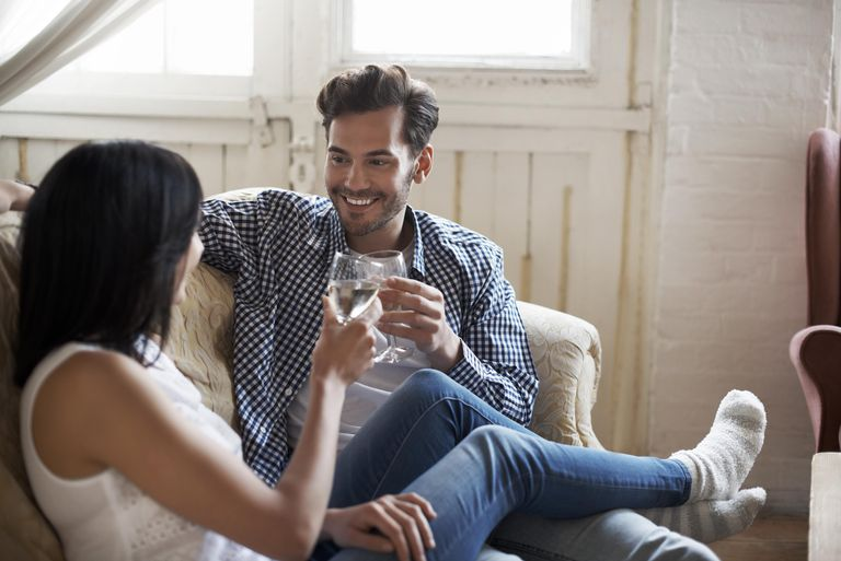 Couple sitting on sofa talking and drinking wine