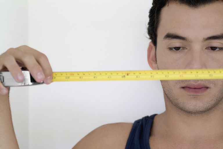 Close-up of a man holding a measuring tape