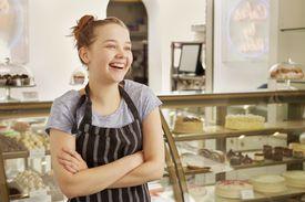 Girl working in bakery looking away smiling
