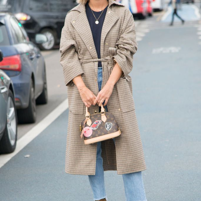 Street style in frayed hem jeans and a trench coat