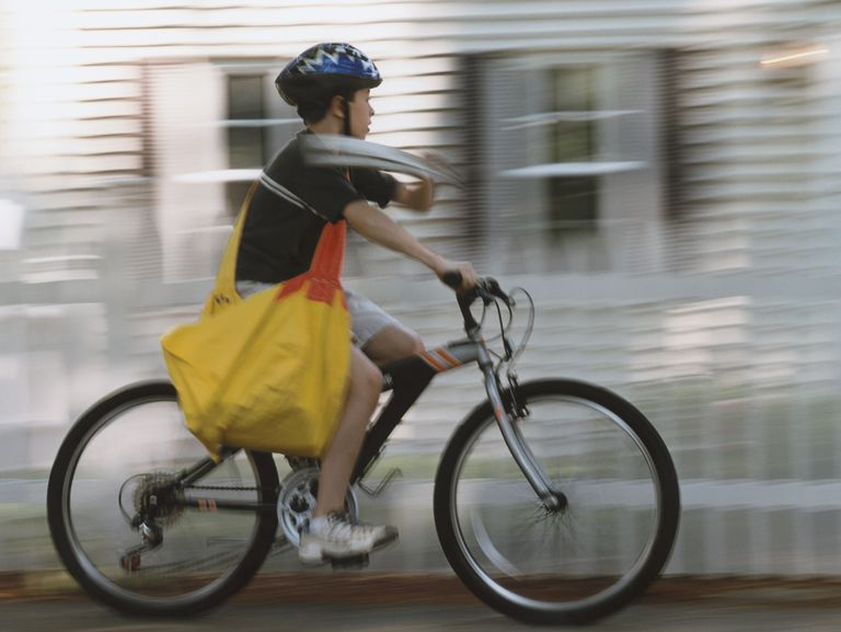 Newspaper delivery boy riding bike working under his state's child labor laws.