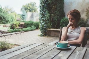 A woman contemplating her legal separation, taking time to think over a cup of coffee.