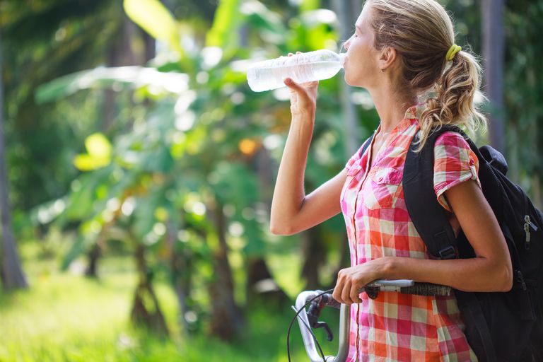 Beautiful young woman drinking water after bicycling