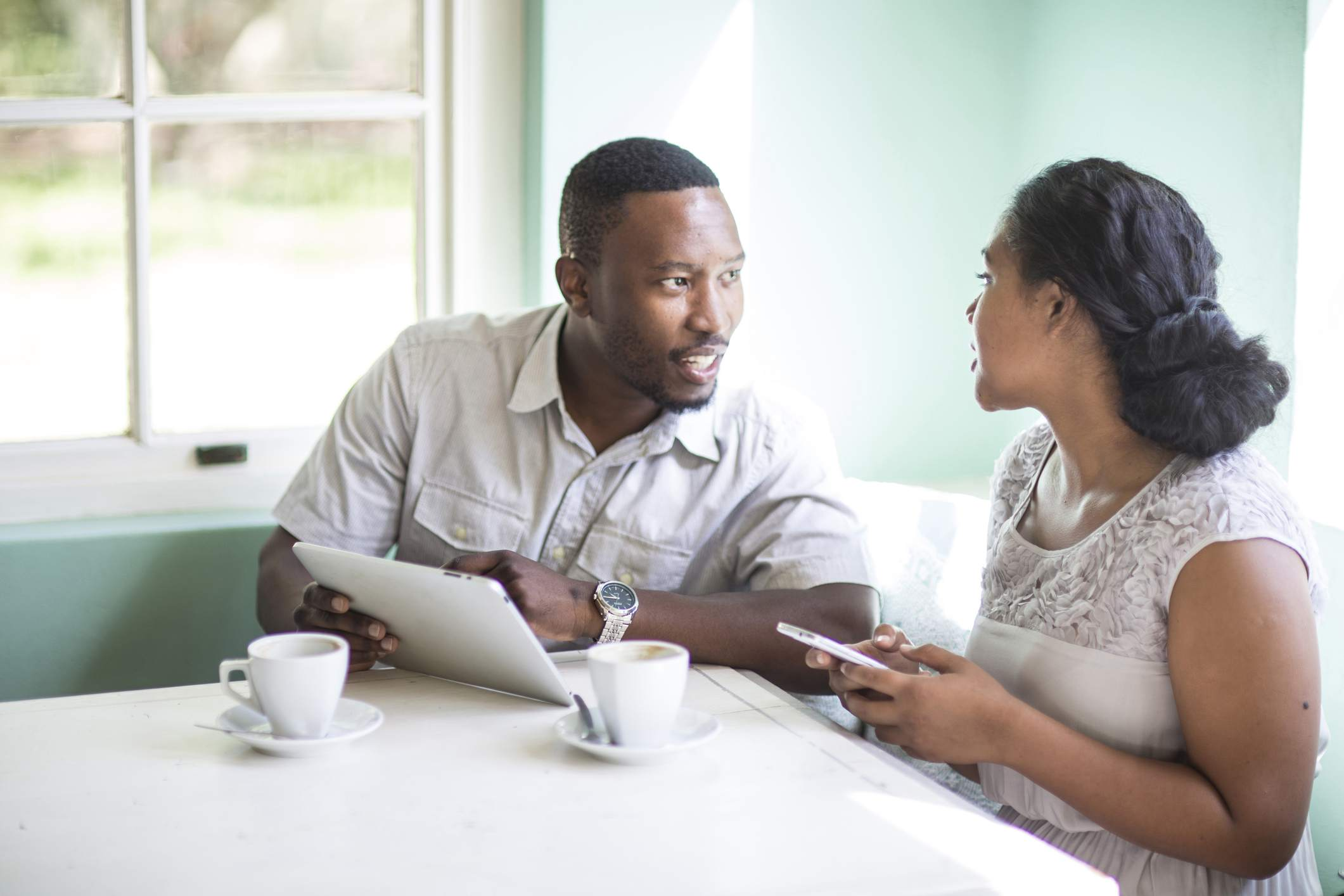 Couple using cell phone and digital tablet at breakfast table