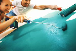 People painting a wall bright turquoise