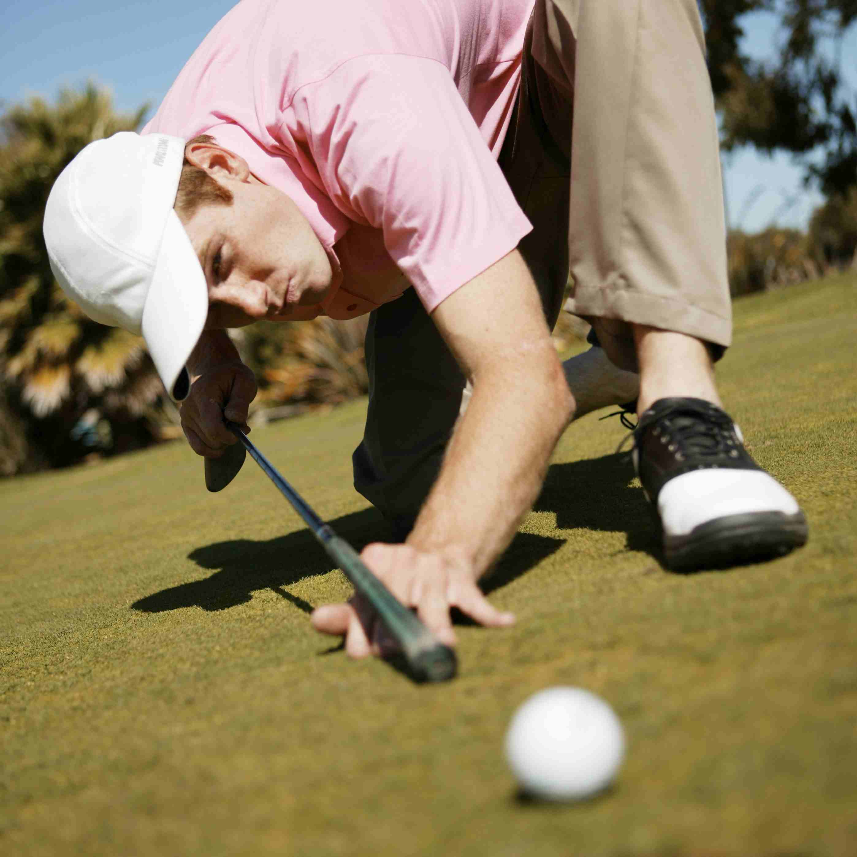 Golfer using his putter like a pool cue on the green