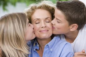 Mother being kissed by son and daughter (13-15) eyes closed, smiling.