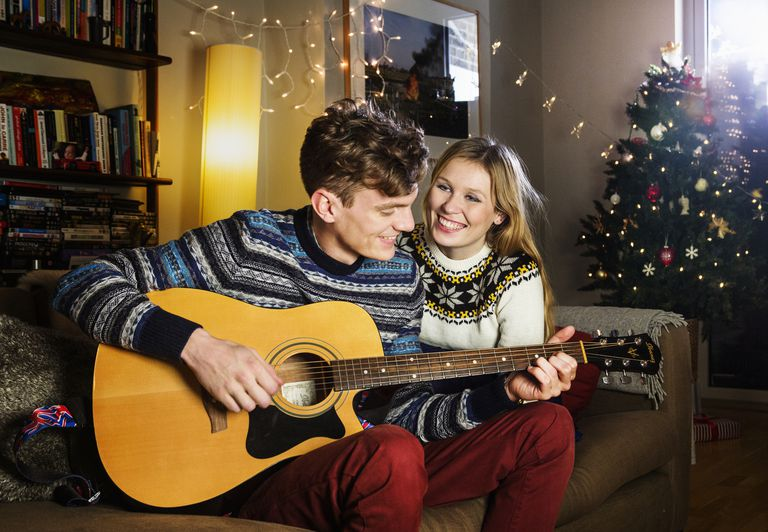 man and woman playing acoustic guitar at christmas