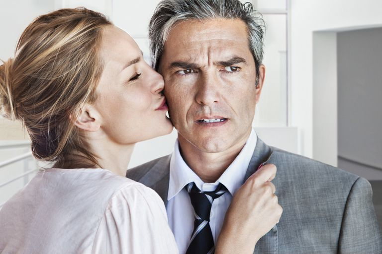 woman kissing man with bothered expression