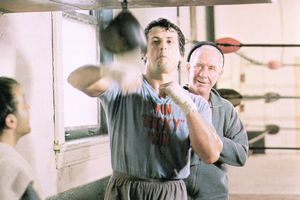 American actor Sylvester Stallone strikes at a punching bag