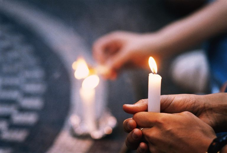Candle being lit at Strawberry Fields, Central Park, New York, USA