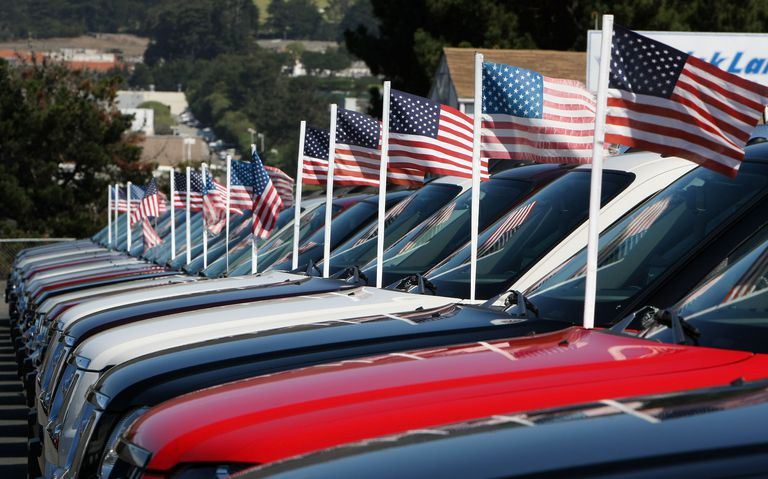 A row of used cars with American flags blowing in the breeze