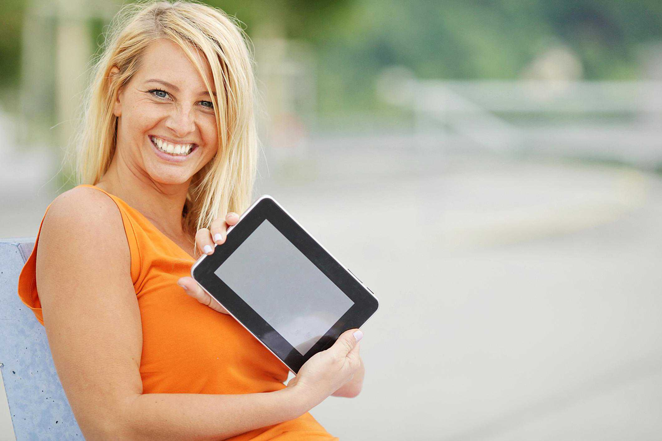 Image of a Woman Happily Holding a Tablet
