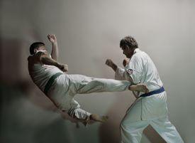 Two men practicing karate kicks