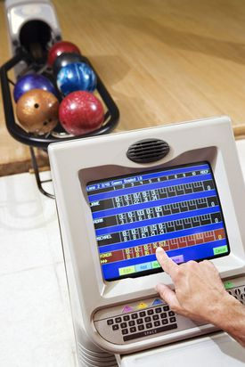 Man touching computer in bowling alley.