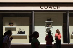 The exterior of a Coach store with onlookers.