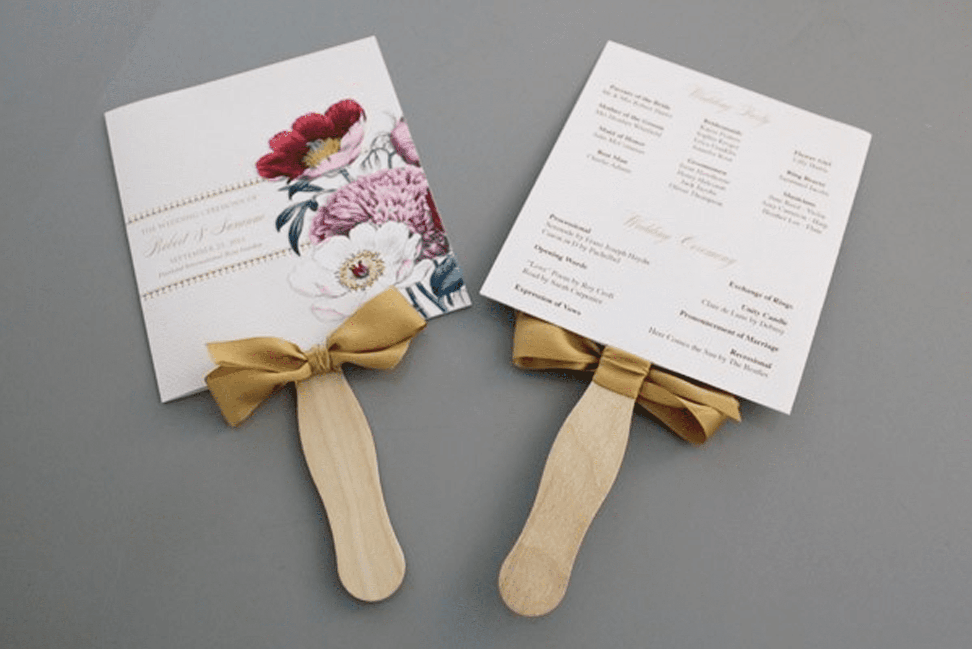 Two paddles with wedding programs attached to them