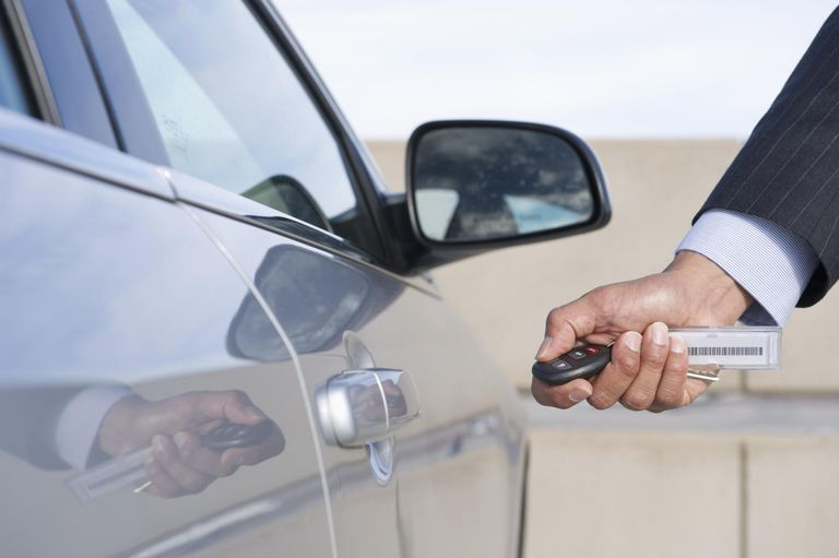 businessman using electronic key to open car door