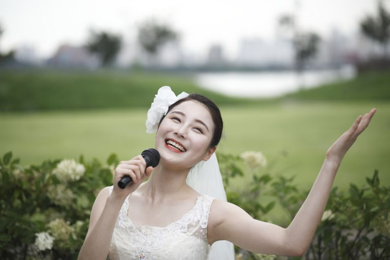 Happy bride singing with microphone