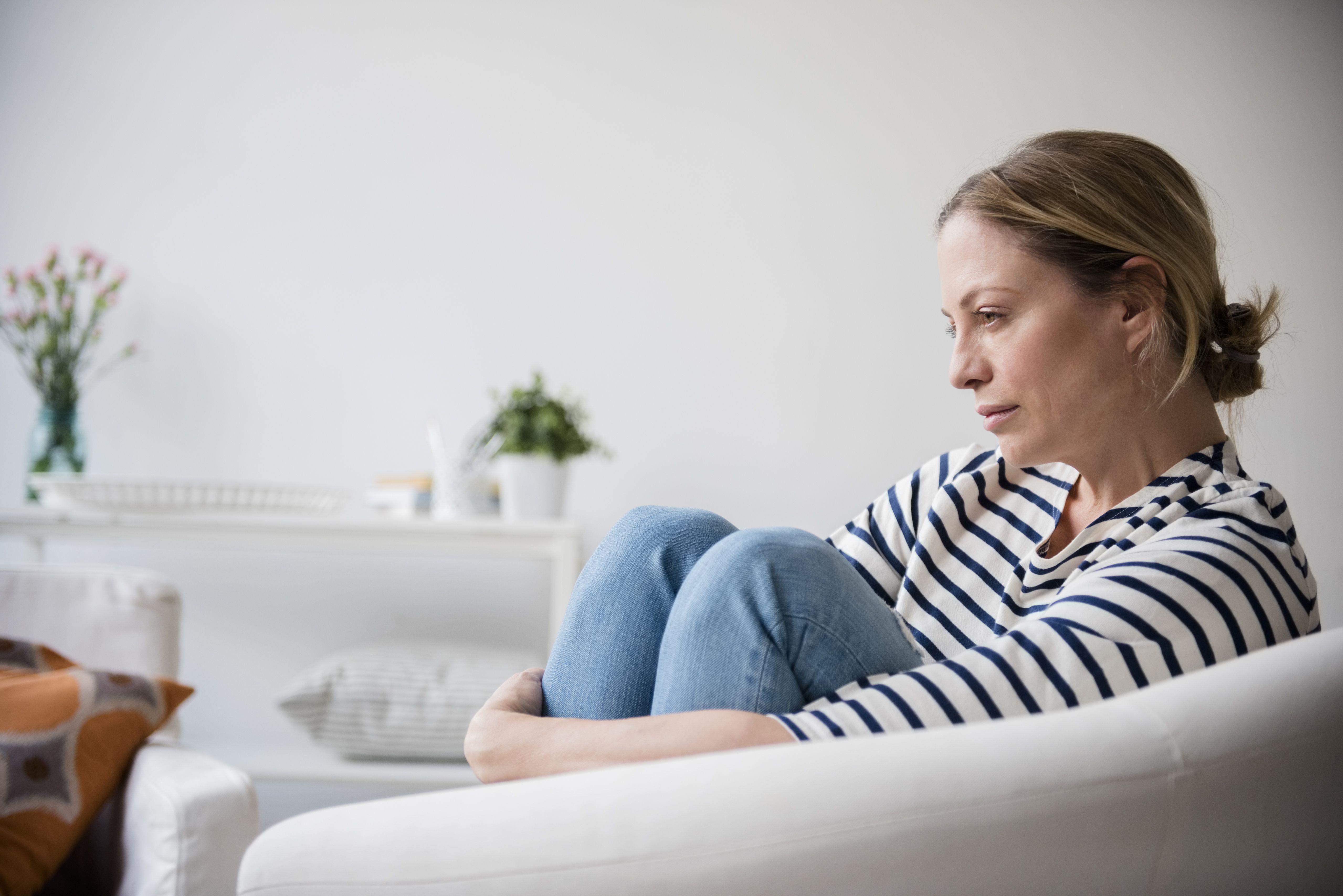 Caucasian woman sitting in armchair holding legs
