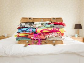 Overpacked suitcase on bed, suburban home
