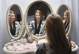 Mature woman looking at reflection in bedside mirror