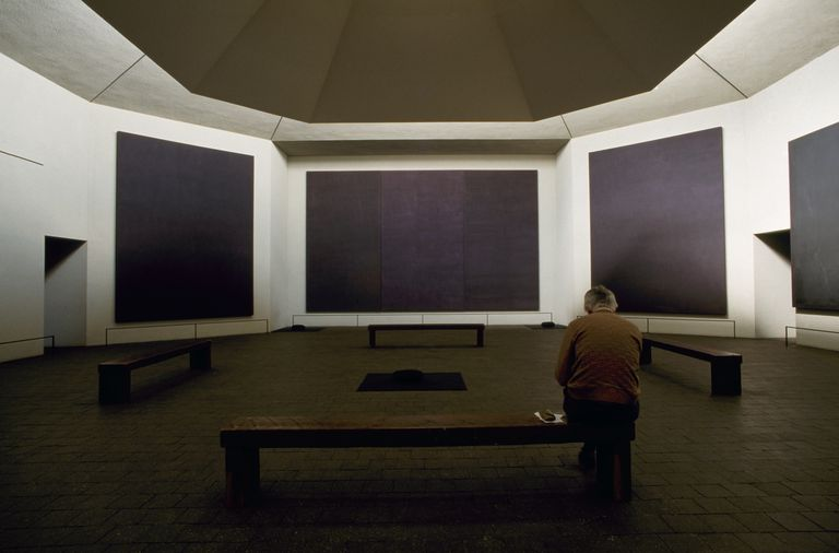 Man sitting in chapel designed by painter Mark Rothko