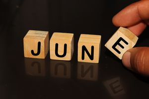 Cropped Hand With June Text On Toy Blocks Against Black Background