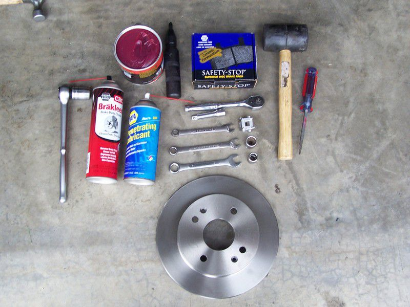Tools and Rear brake pad on cement floor.